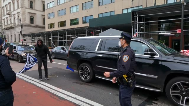 a protester rips a thin blue line american flag off a passing vehicle during an antifascism protest on 5th avenue in midtown manhattan on october 25... - anti fascism stock videos & royalty-free footage