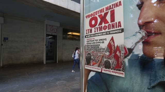 a protester sprays graffiti reading oxi encouraging voters to vote no over a nai poster encouraging voters to vote yes at an anti austerity rally... - referendum stock-videos und b-roll-filmmaterial