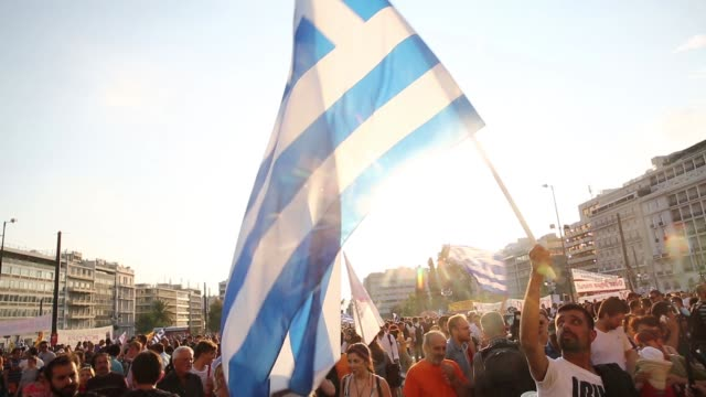 a protester waves a greek national flag during an antiausterity demonstration in support of the greek government in syntagma square in athens greece... - krise stock-videos und b-roll-filmmaterial