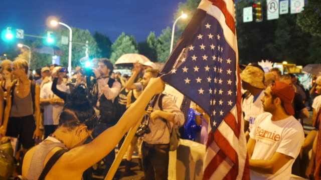 protester waves an upside down american flag near the entrance to the democratic national convention as hillary clinton accepts the nomination on the... - 2016 united states presidential election stock videos & royalty-free footage