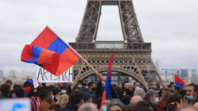 """protester waves the armenian flag as another holds a sign that reads """"reconize artsakh"""" the eiffel tower in the background during a demonstration... - osteuropäische kultur stock-videos und b-roll-filmmaterial"""