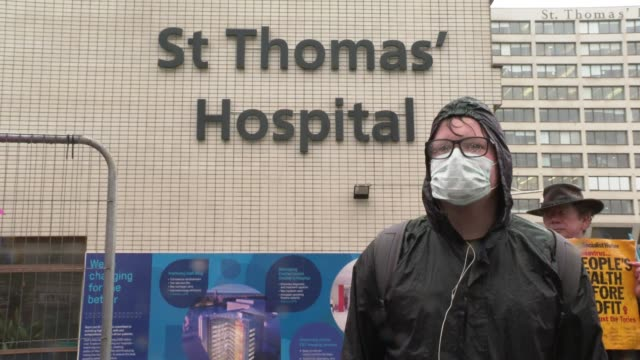 protester wearing a face mask on the pouring rain outside st thomas hospital as he attends a minute's silence on april 28, 2020 in london, england.... - addition key stock videos & royalty-free footage