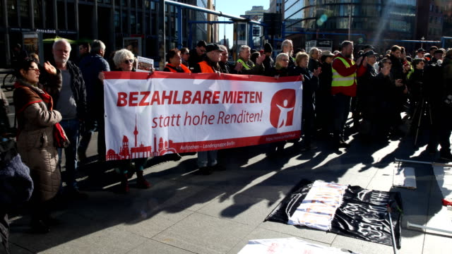 """protester with a banner with the inscription: """"affordable rent instead of high returns"""" supporters of the new left-wing """"stand up"""" movement gather at... - links platz stock-videos und b-roll-filmmaterial"""