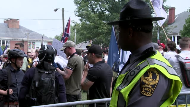 """protesters and an africian american police officer during the """"unite the right"""" rally in charlottesville, virginia. - シャーロッツビル点の映像素材/bロール"""