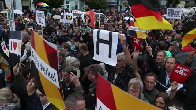 Protesters and hecklers chant 'Merkel muss weg' and 'Volksverraeter' while holding up letters that read 'Get lost' at the edge of an election...