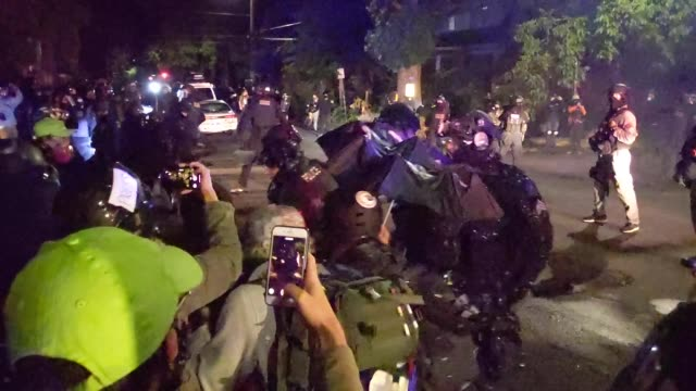 protesters and portland police face off while dispersing a crowd gathered in front of the portland police bureau north precinct early in the morning... - portland oregon video stock e b–roll