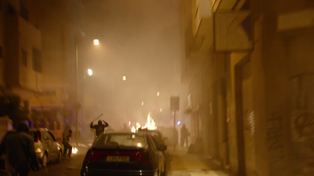 protesters and riot police fighting, greek town square - night - ribellione video stock e b–roll
