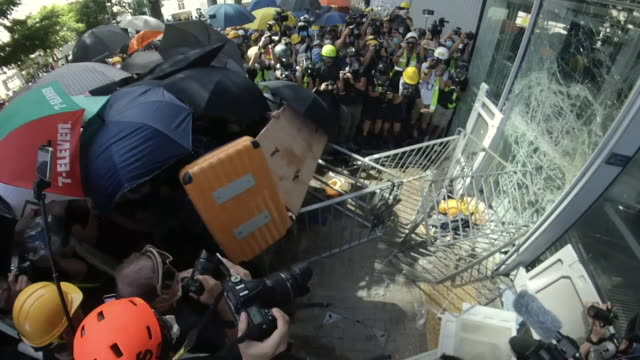 protesters, angry over the proposed extradition law, breaking through the window of the hong kong legco parliament building - hong kong stock videos & royalty-free footage