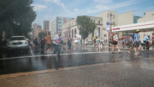 vídeos y material grabado en eventos de stock de protesters are cooled down by open fire hydrants spraying water from sprinklers on broad street during the march to fdr park for bernie sanders on... - philadelphia pennsylvania