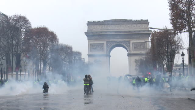 protesters at arc de triomphe with smoke bombs going off and being fired - smoke physical structure stock videos & royalty-free footage