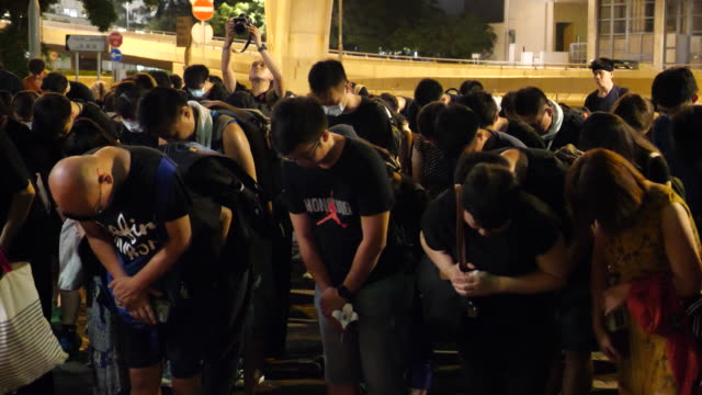 protesters attend a memorial service at legco for the protestor who committed suicide and left a note related to protests - gottesdienst stock-videos und b-roll-filmmaterial