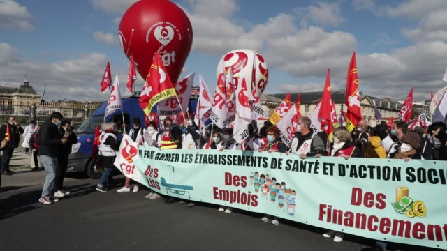 protesters behind a banner during a day of mobilization and national strike in the health, medico-social and social sectors to ask for more resources... - rettungsdienst mitarbeiter stock-videos und b-roll-filmmaterial