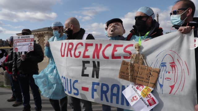 """protesters behind a banner reading """"suffering emergencies"""" and holding a puppet which represents emmanuel macron smoking a cigar pictured during a... - rettungsdienst mitarbeiter stock-videos und b-roll-filmmaterial"""