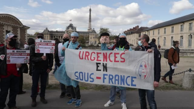 """protesters behind a banner reading """"suffering emergencies"""", the eiffel tower in the background during a day of mobilization and national strike in... - rettungsdienst mitarbeiter stock-videos und b-roll-filmmaterial"""