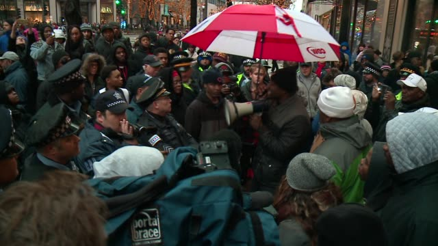 protesters block police and shoppers from nike store on michigan avenue on black friday in the wake of the release of the video showing the shooting... - sportschuh stock-videos und b-roll-filmmaterial