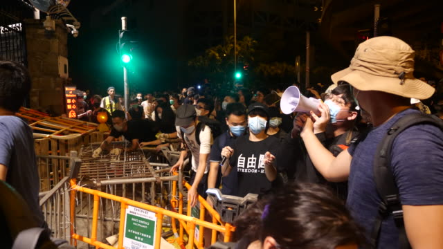 protesters build barricades and taunt the police during a late night siege of the hong kong police headquarters - umgeben stock-videos und b-roll-filmmaterial