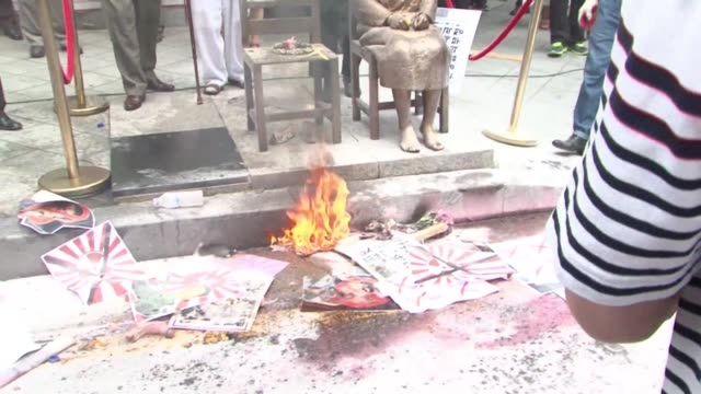protesters burn abe's portrait outside the japanese embassy in seoul near a bronze statue representing one of the so called comfort women as the... - japanese surrender stock videos and b-roll footage
