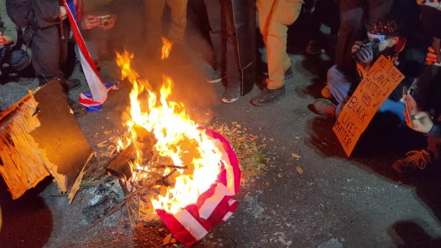 protesters burn an american flag in front of the mark o hatfield us courthouse in the early morning on august 1 2020 in portland oregon portlands... - burning stock videos & royalty-free footage