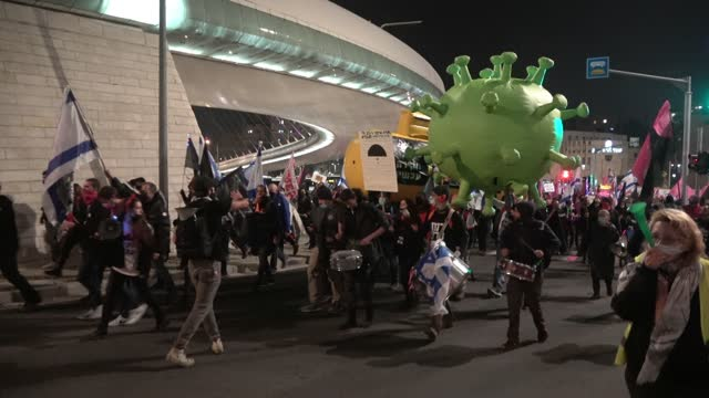 protesters carry a giant mock-up of a coronavirus and large submarine mock-ups as they march through downtown jerusalem on their way to the prime... - eddie large stock videos & royalty-free footage