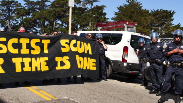 protesters carry a sign reading fascist scum your time is done near alamo square in san francisco california where protesters gathered after members... - anti fascism stock videos & royalty-free footage