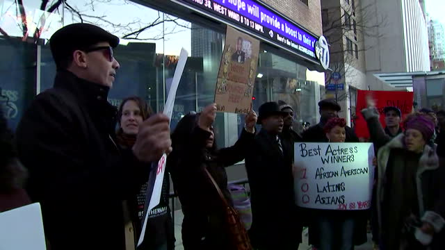 protesters chant and hold signs during rally in new york against racism in the oscars. they stand outside the abc building and demonstrate for racial... - academy awards stock videos & royalty-free footage