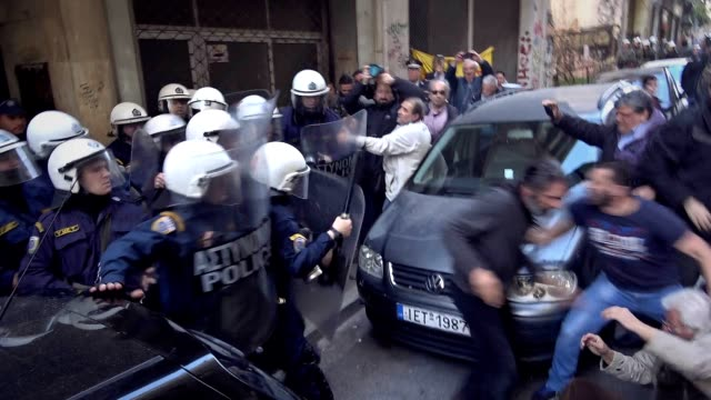 protesters clash with police during rally against housing auctions outside a notary office in athens three protesters were injured among them a woman... - crisis stock videos & royalty-free footage