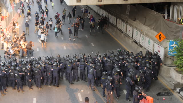 protesters clash with police throwing objects near the myanmar embassy on february 1, 2021 in bangkok, thailand. protesters were angry at the recent... - ミャンマー点の映像素材/bロール