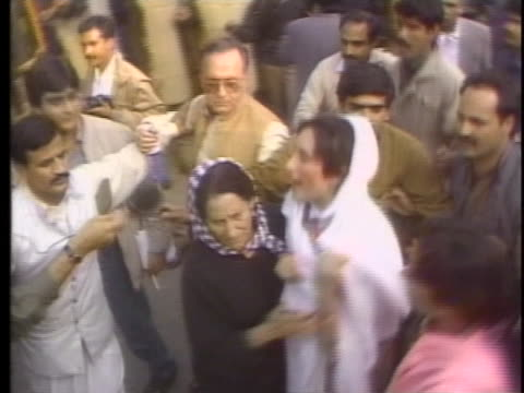 protesters clash with riot police in islamabad, pakistan while ex-premier and former prime minister benazir bhutto walks through the crowd. - (war or terrorism or election or government or illness or news event or speech or politics or politician or conflict or military or extreme weather or business or economy) and not usa stock videos & royalty-free footage