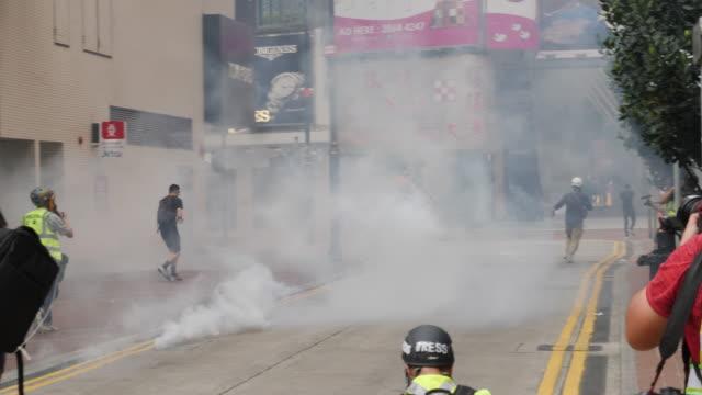 vídeos de stock, filmes e b-roll de protesters gather at causeway bay where police fired tear gas and pepper spray to disperse the crowd - ilha de hong kong