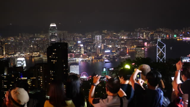 protesters gather at victoria peak for a nighttime protest shining lights and laser pointers - victoria peak stock videos & royalty-free footage