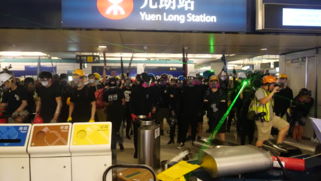 vídeos de stock, filmes e b-roll de protesters gather at yuen long rail station about government inaction to prosecute triads after they assaulted hong kong citizens and protesters... - franja estilo de cabelo