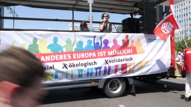 """protesters gather before the start of the demonstration at alexanderplatz with banner inscription: """"another europe is possible"""" and listen to a... - populism stock videos & royalty-free footage"""