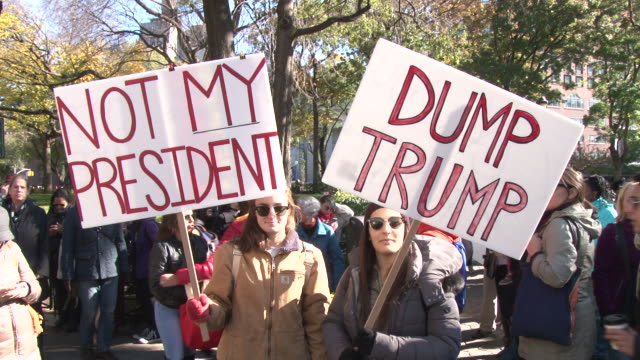 Protesters gather in Union Square before the start of the march to Trump Towers in midtown / People hold signs to voice their dissatisfaction for the...