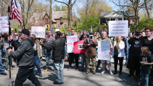 vídeos de stock e filmes b-roll de protesters gather outside indiana governor eric holcomb's mansion in the 4700 block of n. meridian street, to protest what they are describing as,... - michigan