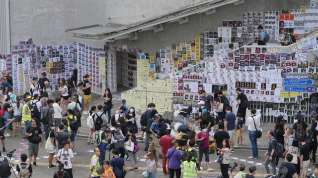 protesters gather outside the government complex in admiralty to put up protest flyers all over the lennon wall - regierung stock-videos und b-roll-filmmaterial