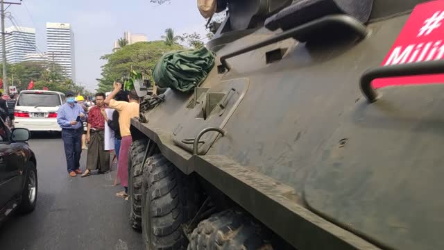 protesters gather to protest against the military coup near an armored personnel carrier parked outside the central bank of myanmar, as they gather... - ミャンマー点の映像素材/bロール