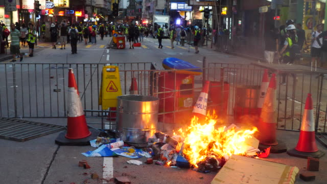 protesters gathered and blocked harcourt road near government complex and threw molotov cocktails and bricks at police who fired tear gas and water... - 放水砲点の映像素材/bロール