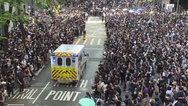 protesters give way to an ambulance in hong kong as thousands surround the police headquarters in wanchai demanding for chief executive carrie lam to... - wanchai stock videos and b-roll footage