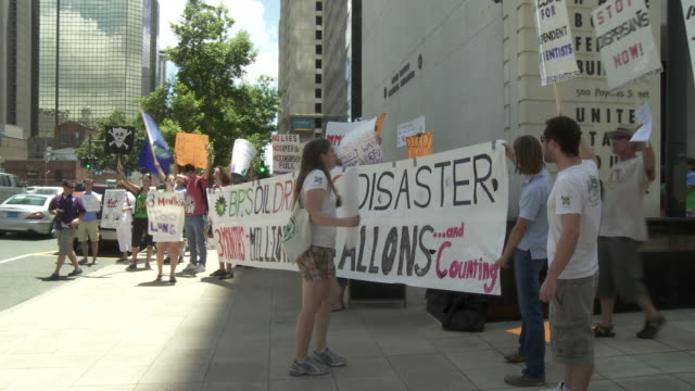 Protesters hold a demonstration against BP while holding banners and signs.