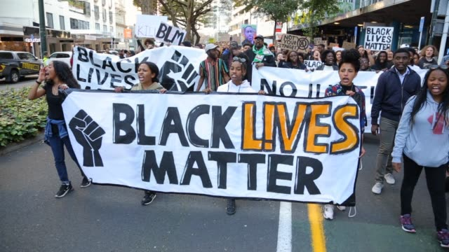 protesters hold a large long banner stating black lives matter and chant while they march through the city during a protest in support of the black... - soziale gerechtigkeit stock-videos und b-roll-filmmaterial