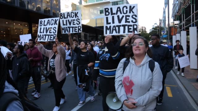 stockvideo's en b-roll-footage met protesters hold a large long banner stating black lives matter and chant no justice no peace as they march through the city during a protest in... - chanten