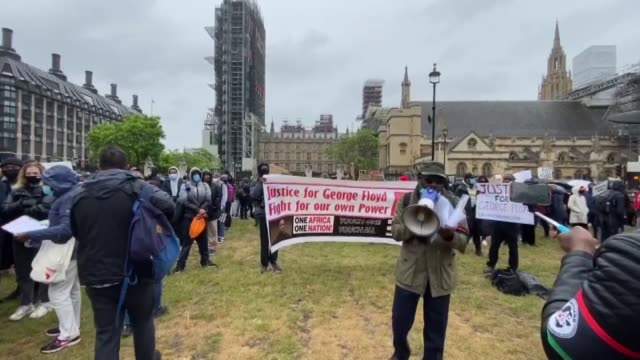 protesters hold placards as they attend a demonstration in parliament square in central london on june 6 to show solidarity with the black lives... - protestor stock videos & royalty-free footage