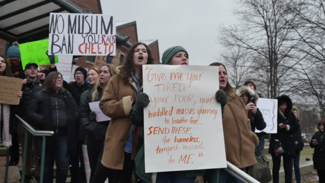 """stockvideo's en b-roll-footage met protesters hold signs and chant that refugees are welcome outside the city hall building in bloomington, ind. after a """"no ban! no wall!"""" rally. the... - chanten"""