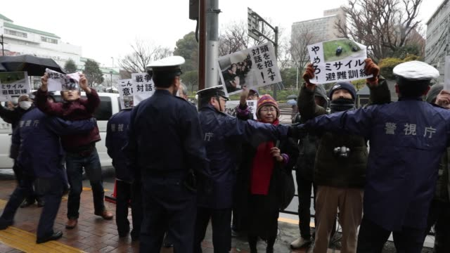 protesters hold signs as police officers form a cordon during a missileattack drill in tokyo japan on monday jan 22 members of the media assemble to... - allarme di prova video stock e b–roll