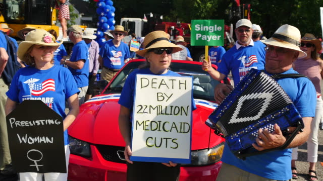 protesters hold signs in support of universal healthcare before the 4th of july parade in bloomington indiana one sign reads preexisting woman while... - medicaid stock videos and b-roll footage
