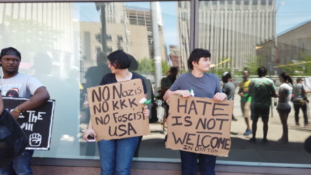 protesters hold signs while protesting against the kkk hundreds of counter protesters including the nation of islam the dayton chapter of the black... - anti fascism stock videos & royalty-free footage