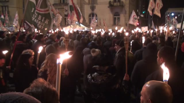 Protesters hold torches and flags of the Jobbik party during an antigovernment protest organized by the opposition Party Jobbik in front of the...