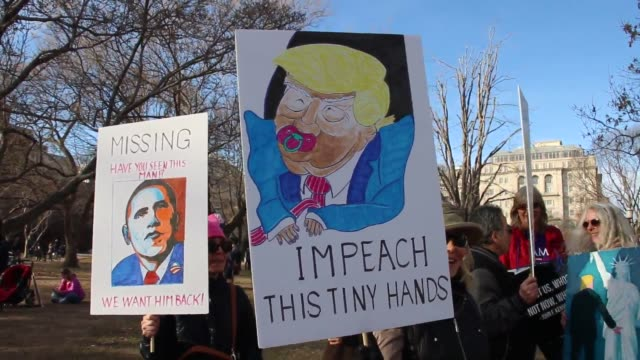 Protesters hold Trump signs at Lafayette Square in front of White House at Women's March in Washington DC