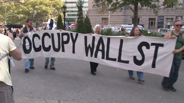 protesters hold up a large banner in battery park, on the one year anniversary of the occupy wall street movement. - occupy protests stock videos & royalty-free footage