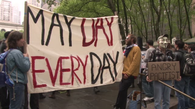protesters hold up a large may day everyday banner at the occupy wall street rally in bryant park nyc - bryant park stock videos and b-roll footage
